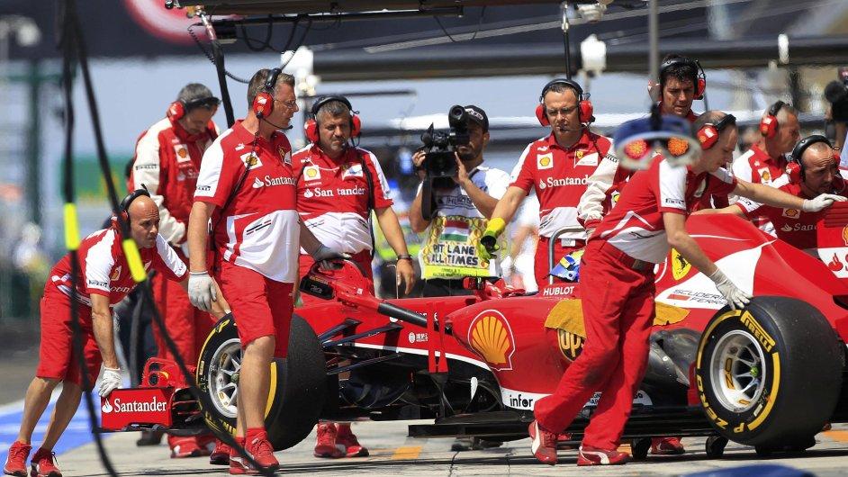 Mechanici stáje Ferrari s vozem Fernanda Alonsa