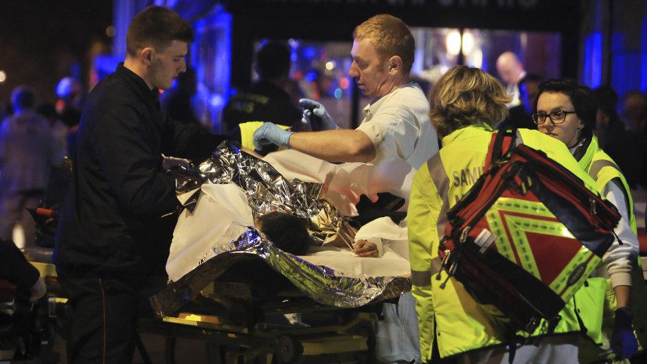 Francouzští záchranáři evakuují zraněné z klubu Bataclan po sérii bombových útoků.