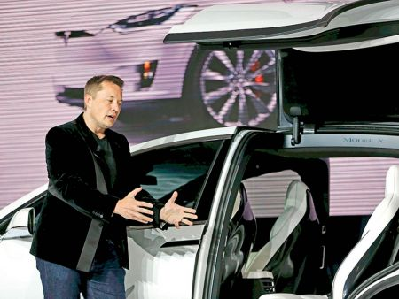 Tesla Motors CEO Elon Musk introduces the falcon wing door on the Model X electric sports-utility vehicles during a presentation in Fremont