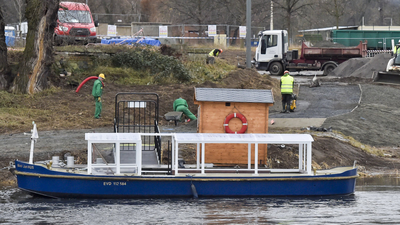Dělníci staví přístupovou cestu k molu přívozu, nahrazujícímu zřícenou lávku v pražské Troji.