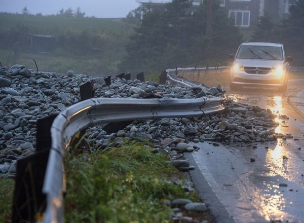 A guard rail was damaged by powerful waves that drove rocks on shore in Cow Bay