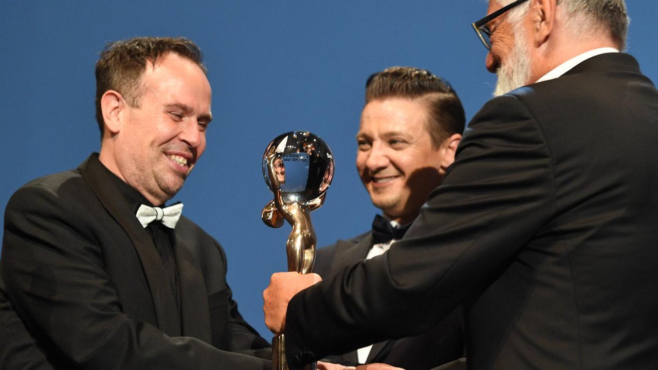 Režisér Křižáčka Václav Kadrnka (vlevo) od prezidenta festivalu Jiřího Bartošky (vpravo) přebírá cenu pro nejlepší film. Uprostřed je hollywoodský herec Jeremy Renner.