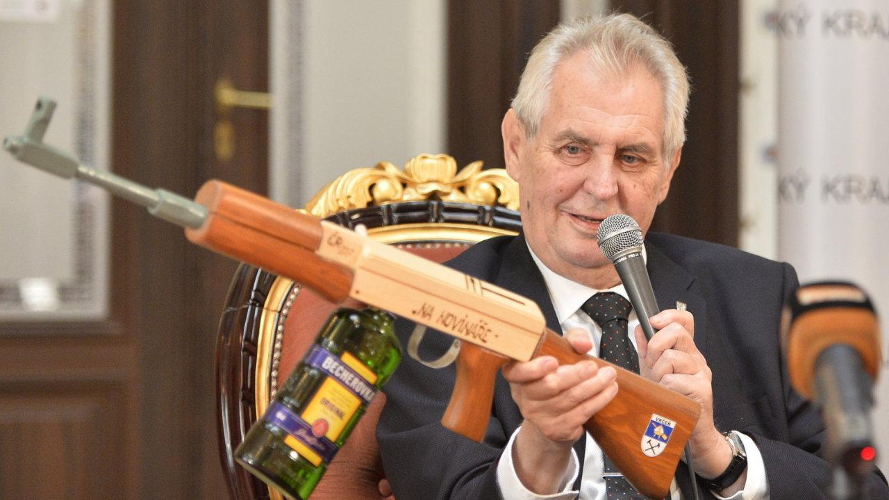 Zeman předvedl dřevěný samopal. Má zásobník na Becherovku a je určený na novináře.
