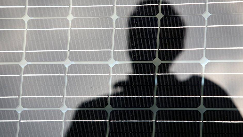 Ilustrační foto - Solární panel a na něm silueta muže