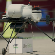 Dron Uber nakládá zásilku s jídlem.