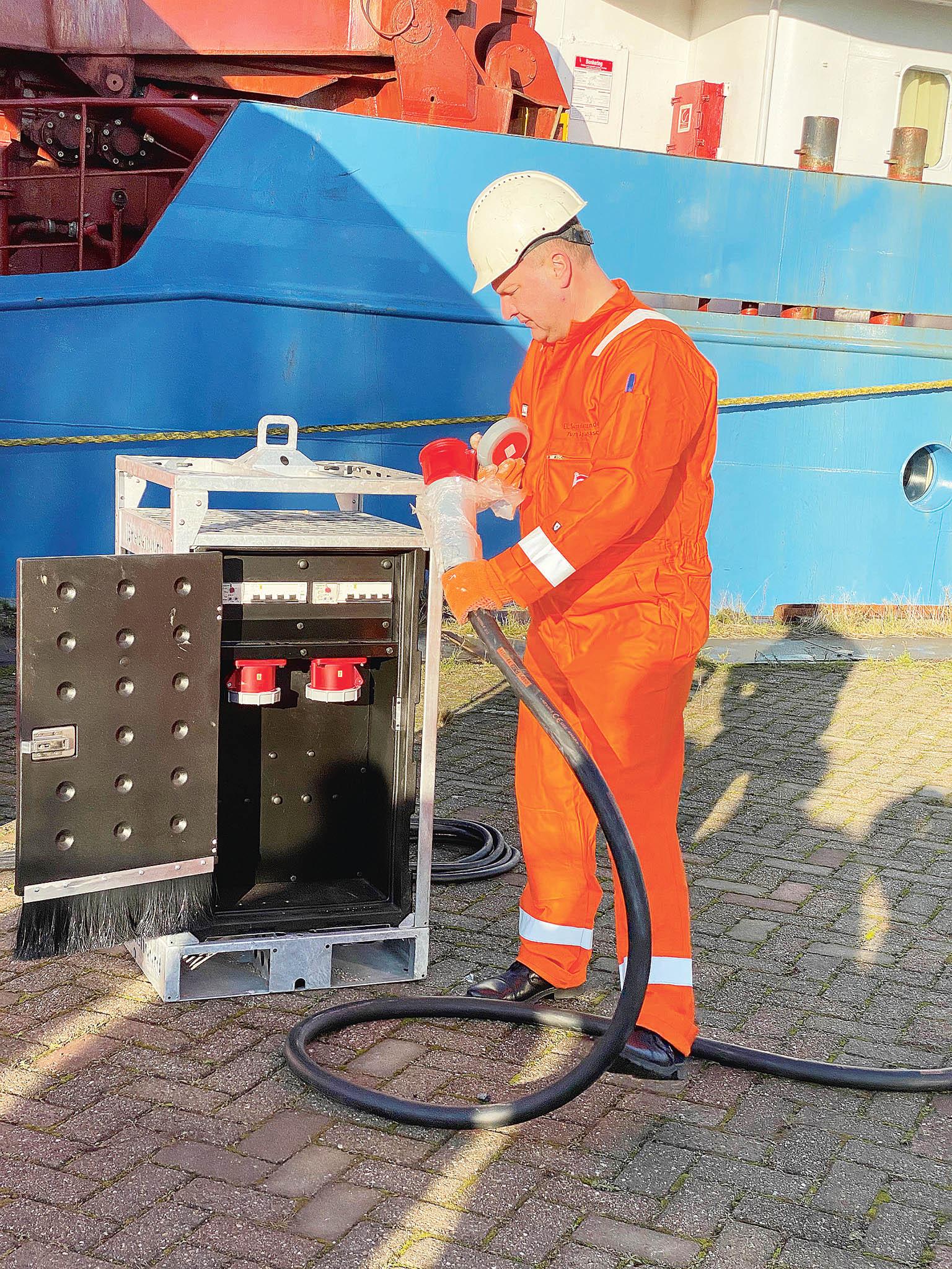 Připojování lodě doelektrické zásuvky namolu vrotterdamském přístavu.