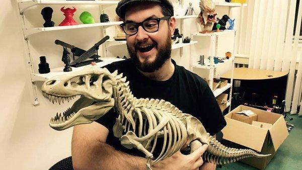 Josef Průša drží v náručí kostru dinosaura vytištěnou na své tiskárně.