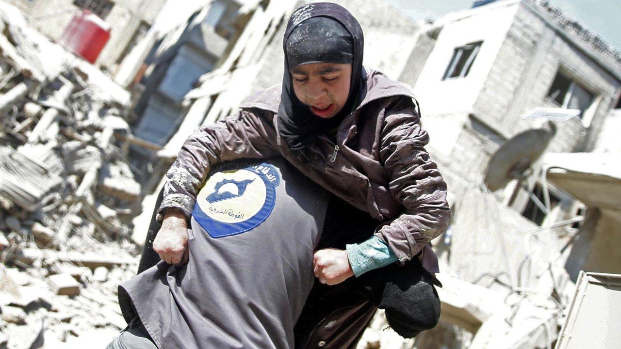 Záchranář drží vnáručí zraněnou dívku veměstě Hamouriyeh vevýchodní Ghútě. UNICEF uvedl, že