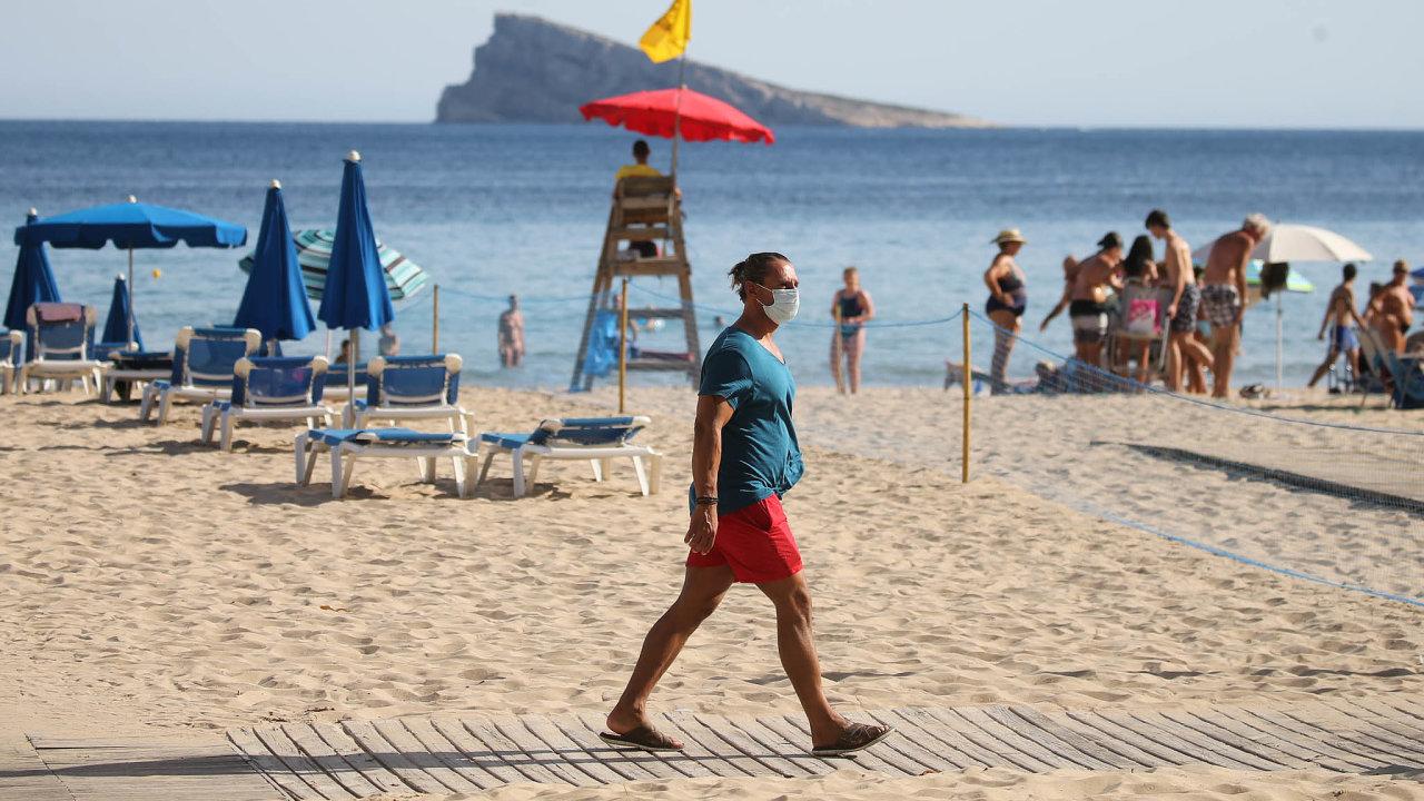Roušky ano i ne. V novém ataku koronaviru jsou na španělských plážích vídáni lidé s rouškami i bez nich.