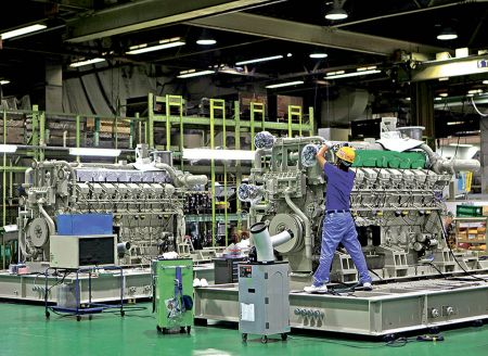 Workers are seen at the assembly line of the company's gas engine generator at Mitsubishi Heavy Industries Sagamihara plant in Sagamihara