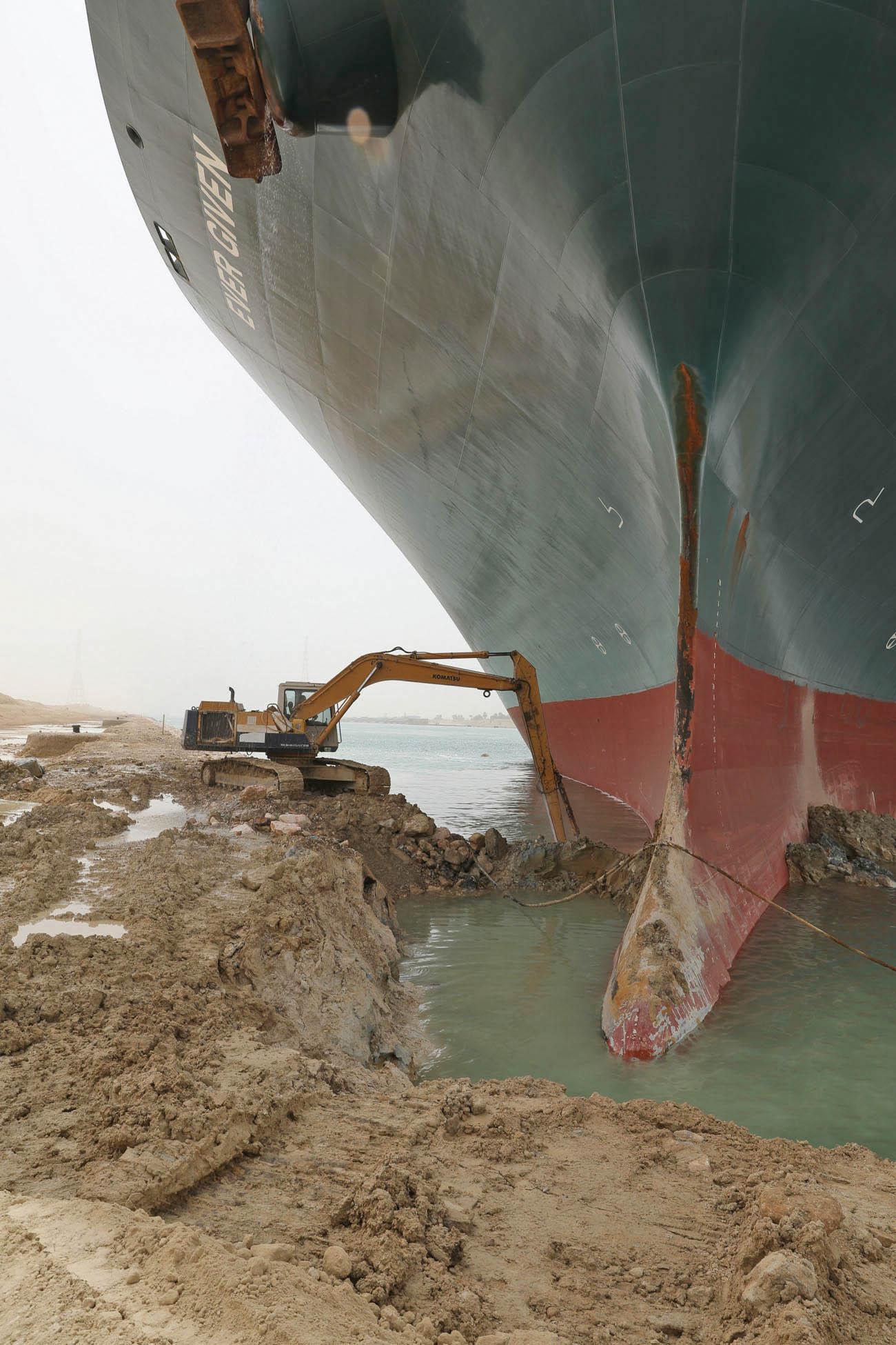 Bagr pracuje naodstraňování písku zpod přídě plavidla Ever Given. Snímek byl pořízen večtvrtek 25. března.