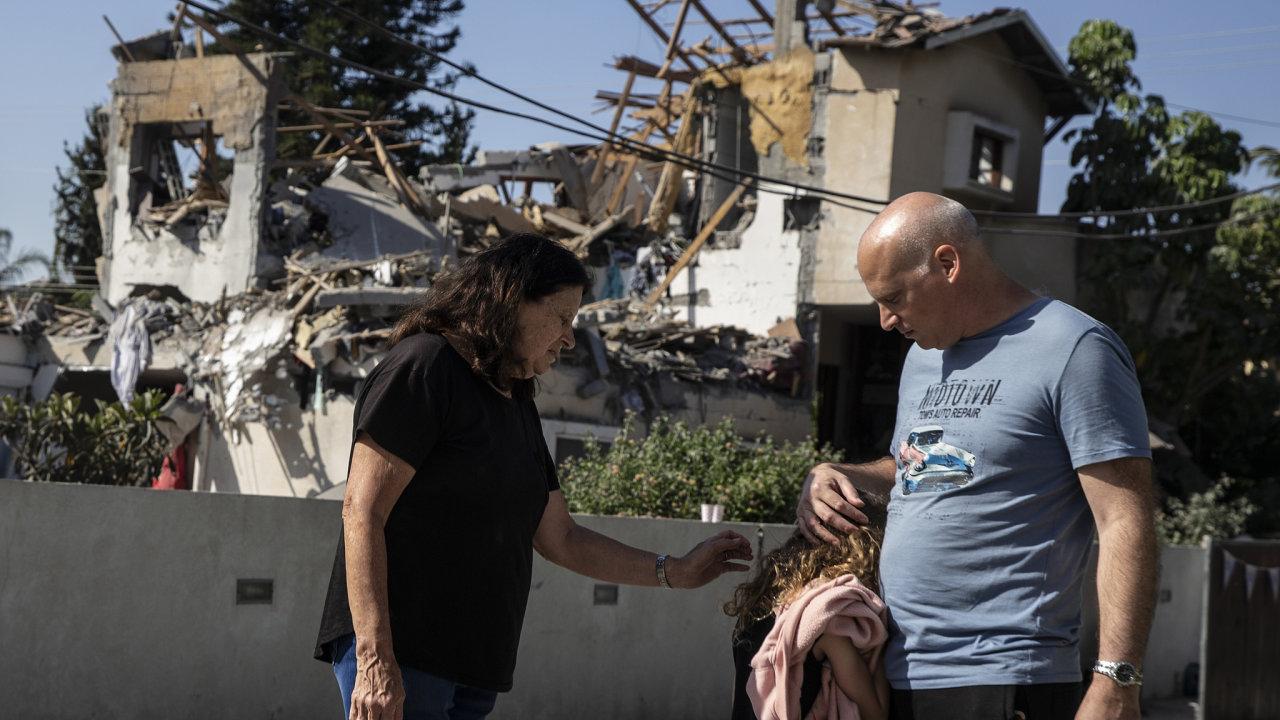 Otec utěšuje svoji dceru u domu poškozeného raketou vystřelenou z Pásma Gazy.