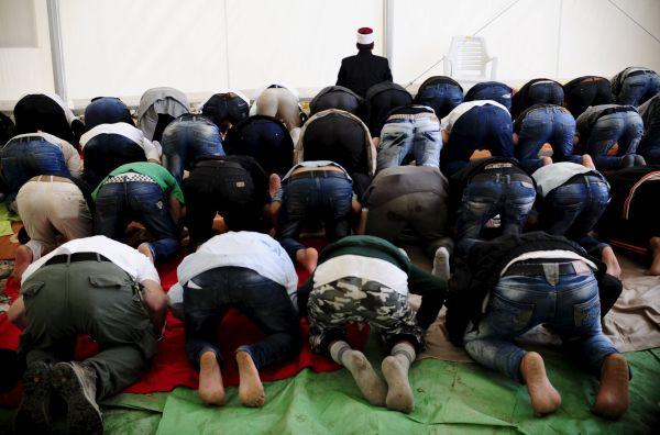 Uprchlíci se modlí během Svátku oběti v uprchlickém táboře v makedonském městě Gevgelija.