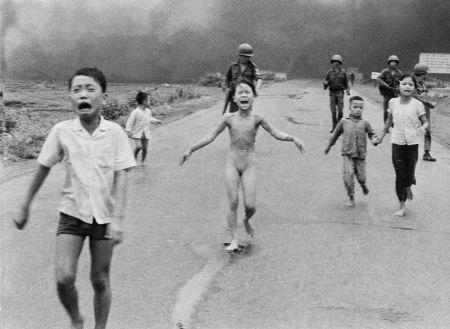 Slavná fotografie dětí popálených napalmem z roku 1972. Uprostřed běží devítiletá Kim se svými bratry, bratranci a sestřenicemi. V pozadí fotky jihovietnamští vojáci.