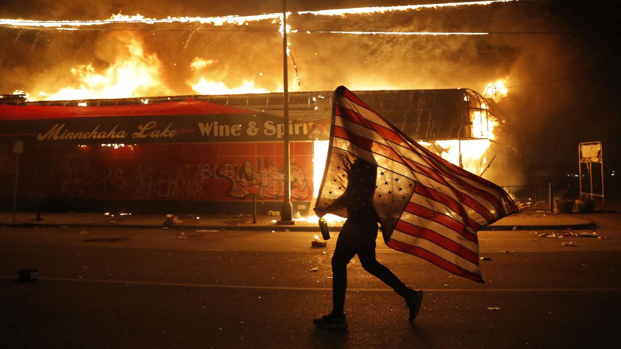 Demonstrant v Minneapolisu nese americkou vlajku obráceně, což bývá vnímáno jako znamení nouze.
