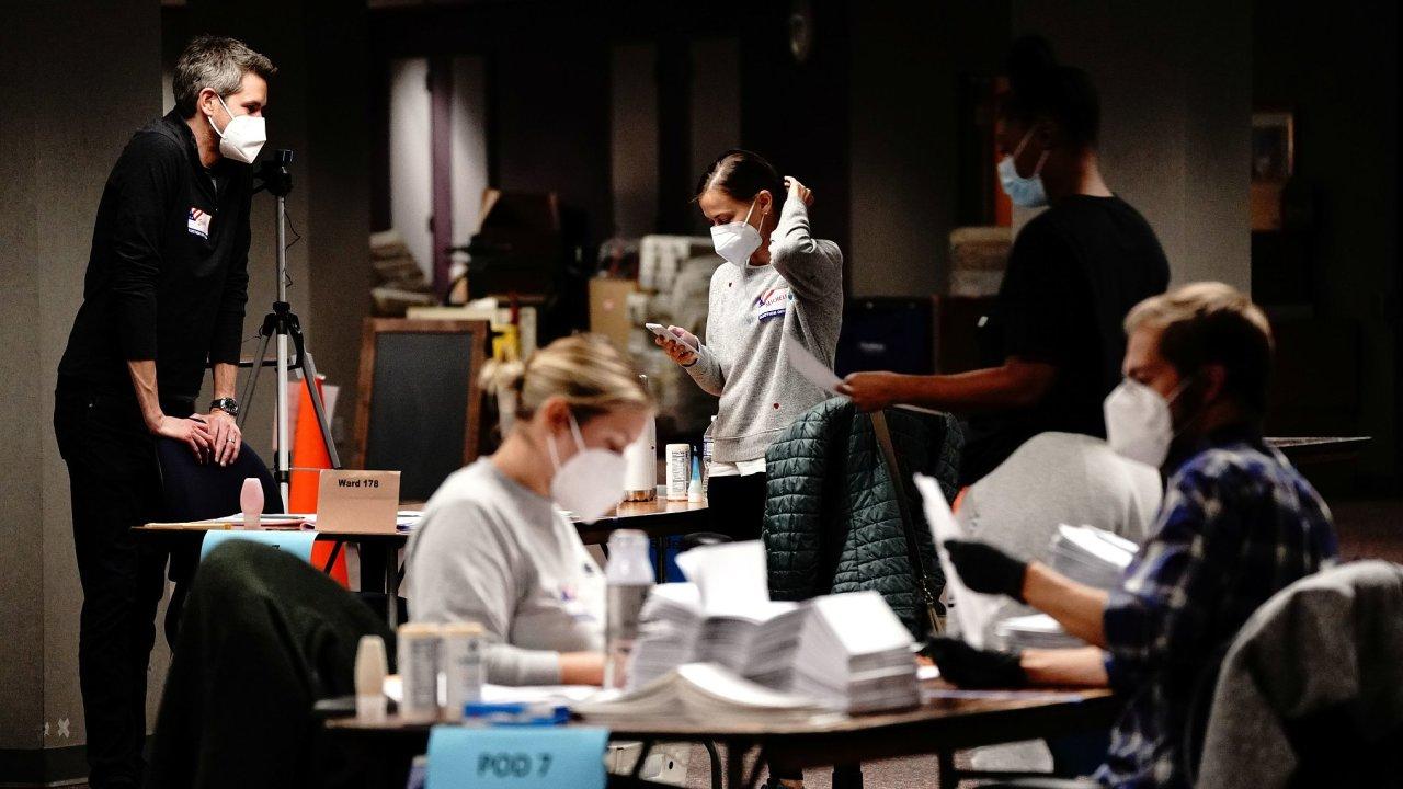 Pracovníci ve volebních místnostech počítají hlasy zaslané poštou.