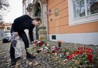 Lidé nosí k budově francouzské ambasády v Praze květiny.