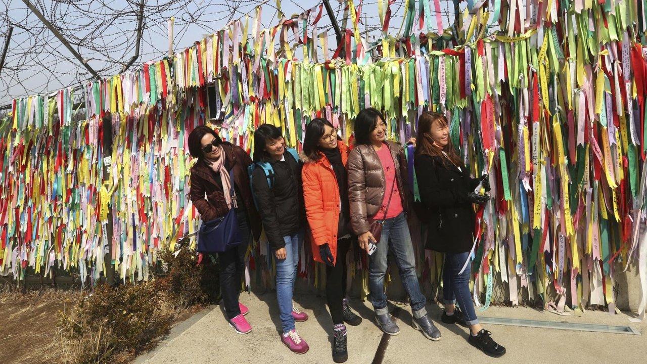 Návštěvníci se skupinově fotí před zdí sostnatým drátem vPchadžu, městě nedaleko hranice se Severní Korejí. Nafáborky lidé upevňují vzkazy spřáním, aby se poloostrov opět sjednotil.