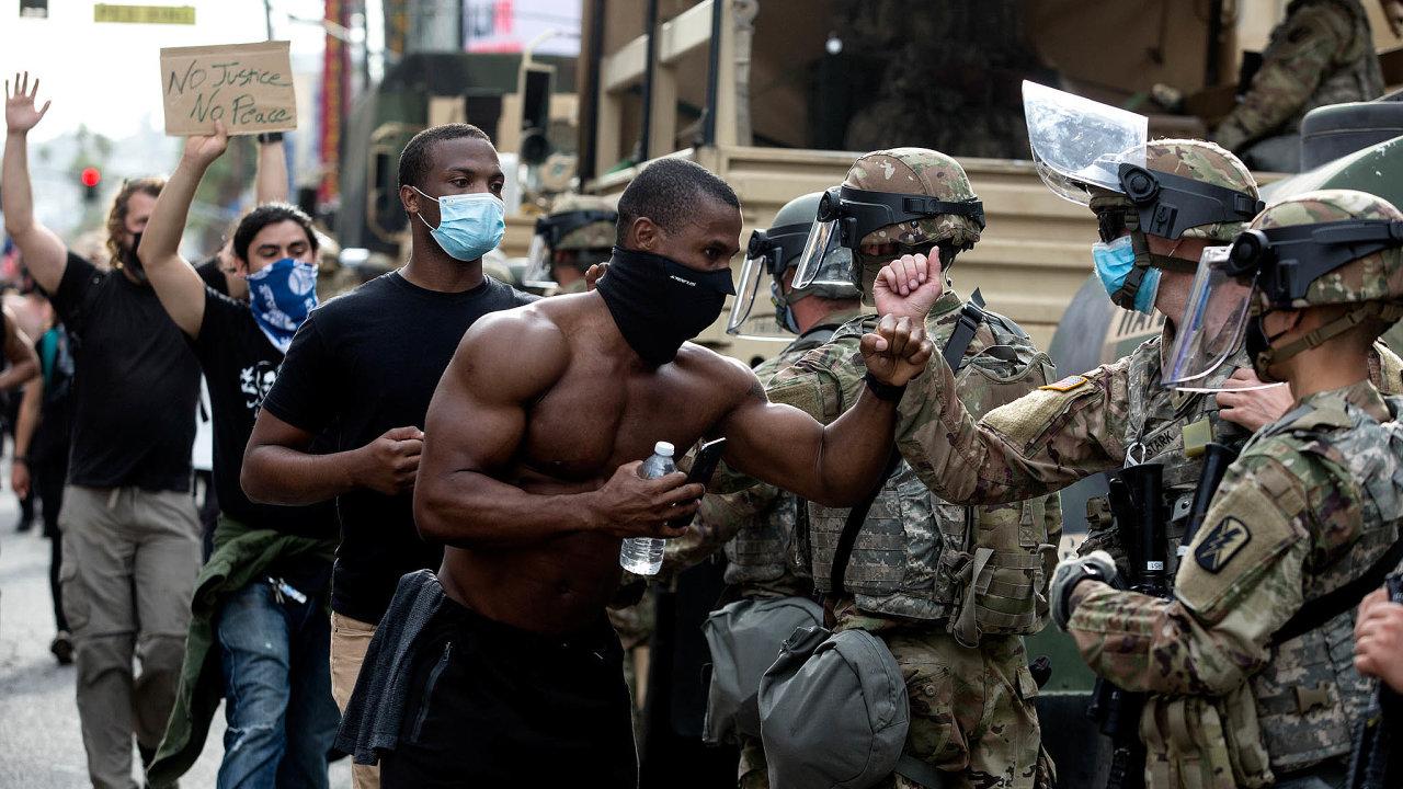 Více než týden trvající demonstrace postupně oslabují amísto násilí protestující spolicií spolupracují. Nasnímku zLos Angeles se demonstranti zdraví spříslušníky Národní gardy.