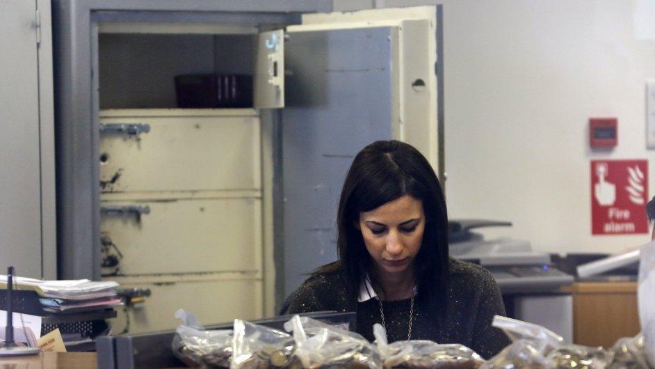 Zaměstnankyně počítá peníze před otevřením kyperské Laiki Bank.