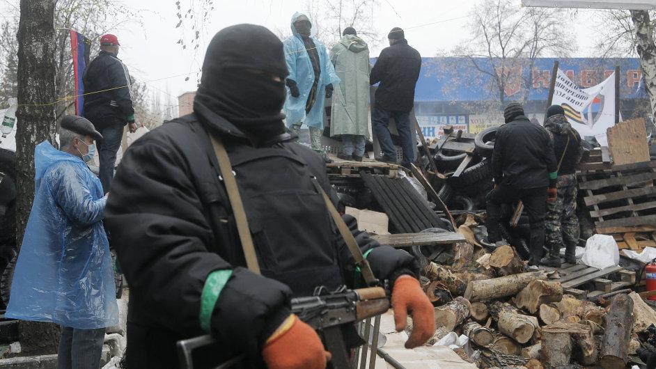 Proruský ozbrojenec drží stráž nad barikádou ve Slavjansku.