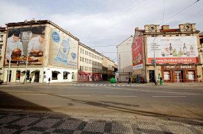 Druhédějství: Nádražní aVltavská ulice. Okolí Anděla je rájem velkých plachet sreklamou. Jejich výskyt graduje vulici Vltavská, kterou proudí automobily knábřeží.