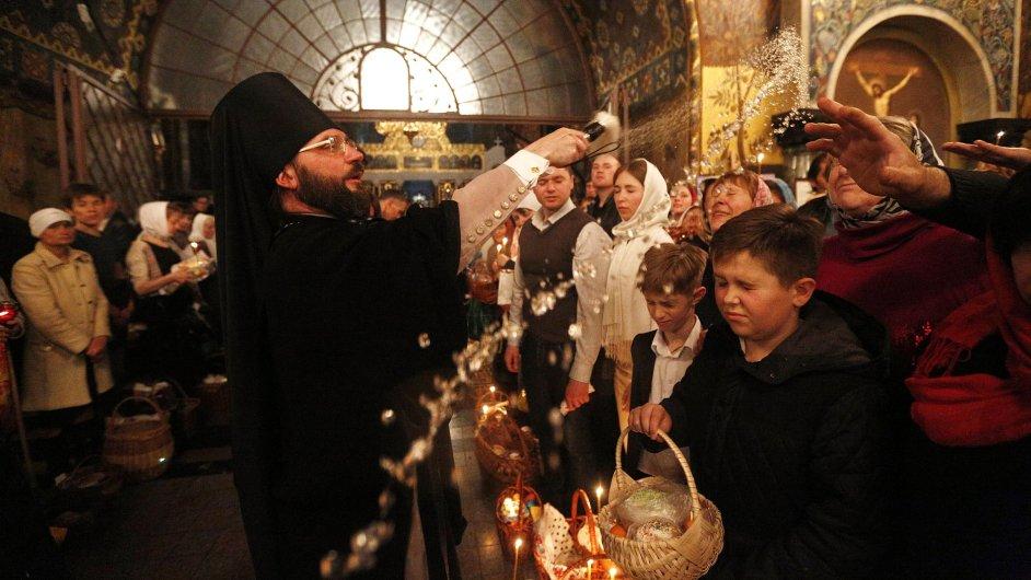 Pravoslavný kněz světí velikonoční pečivo a malovaná vejce v Kyjevě.