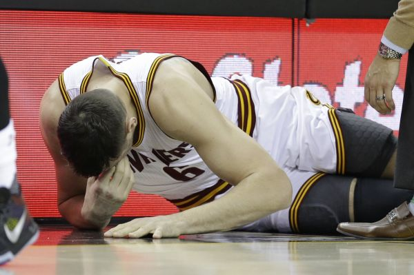 Cleveland Cavaliers' Andrew Bogut (6) grimaces after getting hurt in the first half of an NBA basketball game against the Miami Heat