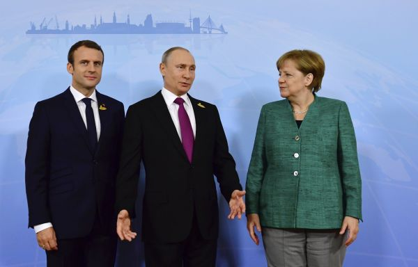 German Chancellor Angela Merkel poses with French President Emmanuel Macron and Russia's President Vladimir Putin (C) prior to a meeting during the G20 summit in HamburgLeaders of the world's top eco