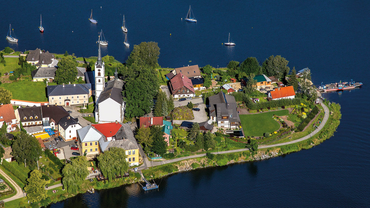 Klidná hladina vodní nádrže Lipno obklopuje malý poloostrov městyse Frymburk.