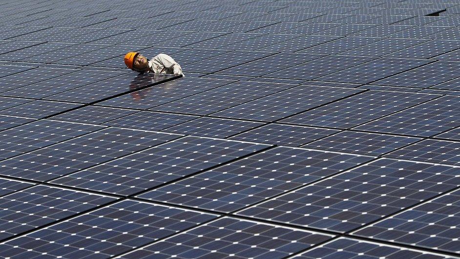 Ilustrační foto - Pracovník kontroluje panely solární elektrárny.