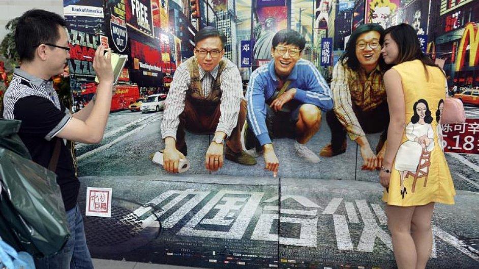 Návštěvníci snímku American Dreams in China v kině provincii Che-pej se fotí s herci na plakátu.