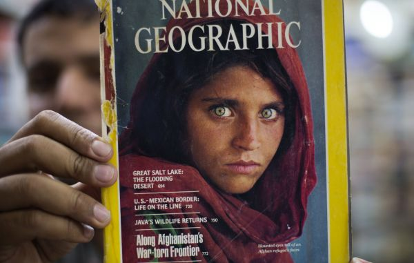 Pakistan's Inam Khan owner of an old books shop shows a copy of a magazine carries photographs of Afghan refugee woman Sharbat Gulla from his rare collection in Islamabad