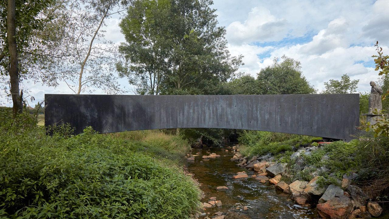 Součástí nové lávky je socha Strážce odprofesora Jana Hendrycha, která přináší dohorizontální krajinné kompozice vertikální prvek aještě zvýrazňuje její duchovní charakter.