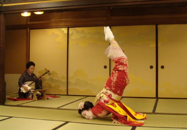 Artistický prvek z tanečního vystoupení gejši. V pozadí hráčka na šamisen.