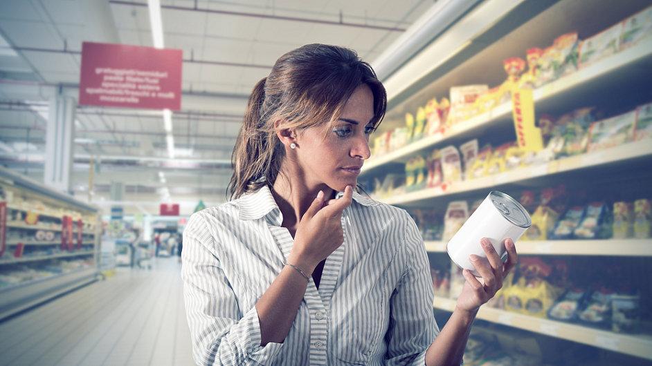 Obchod, zákaznice zkoumá obal na plechovce. Ilustrační foto