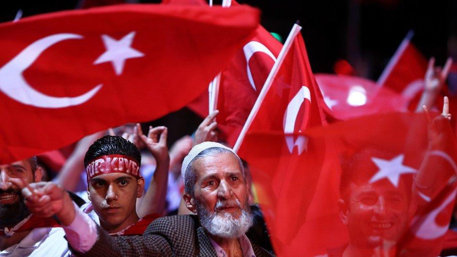 Lidé mávají tureckými vlajkami na Taksimském náměstí v Istanbulu.