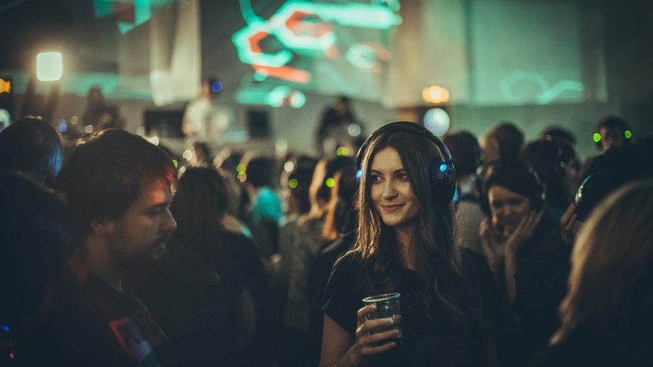 Na tiché party poslouchají lidé hudbu z bezdrátových sluchátek.