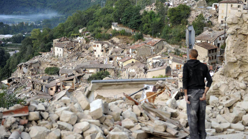 A man observes the rubble in Pescara del Tronto