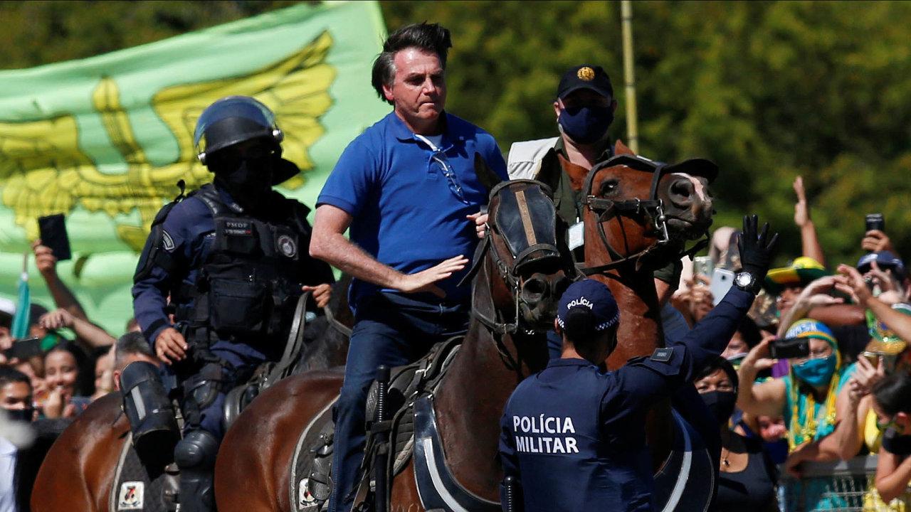 Bizarní obrázky zBrazílie. Prezident Jair Bolsonaro se kekoronaviru staví jinak než většina světa. Karanténa pro něj neexistuje, spříznivci si tiskne ruce, ovíkendu mezi ně dokonce vyjel nakoni.