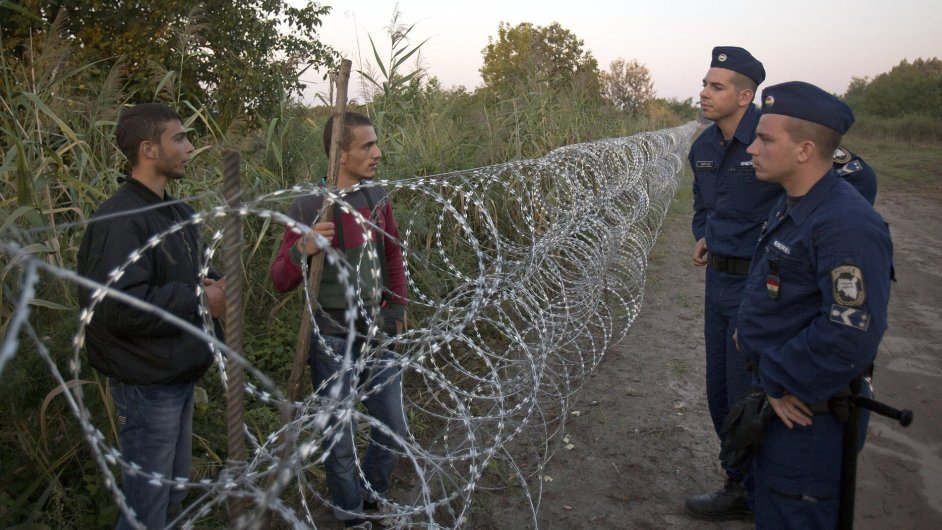 Syrian refugees and Hungarian police chat at the barbed wire fence at the order between Serbia and Hungary