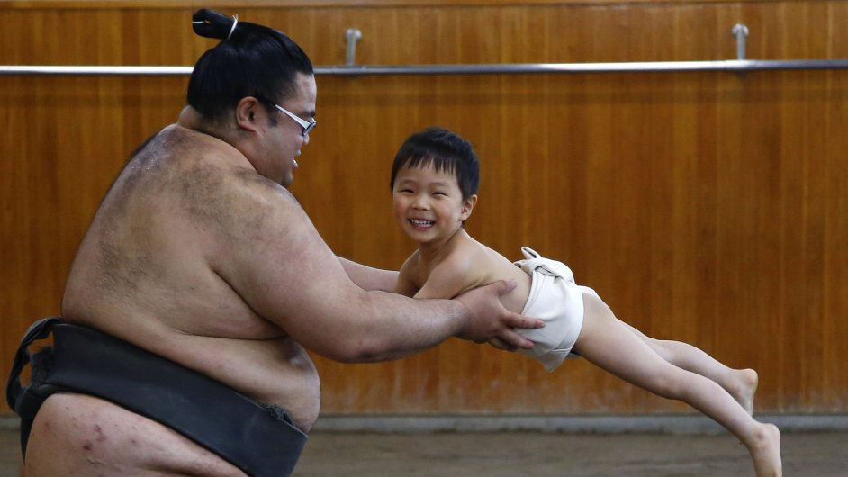 A child plays sumo wrestling with a sumo wrestler during Sumo challenge event in Tokyo
