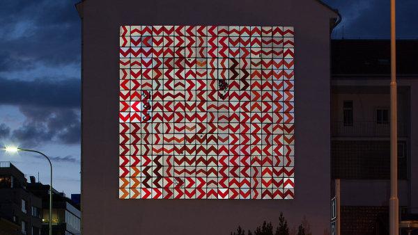 Obří reflexní mozaika vytvořená z ukradených – a nahrazených – značek visí na fasádě jednoho z bytových domů na Smíchově.