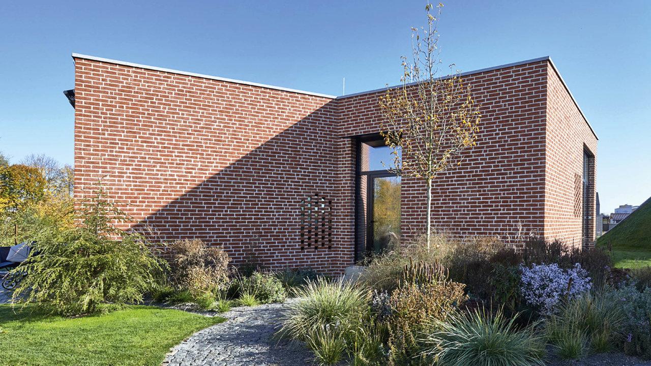 Architektura domu, garáže i zahradní úpravy spolu vytvářejí organickou kompozici.