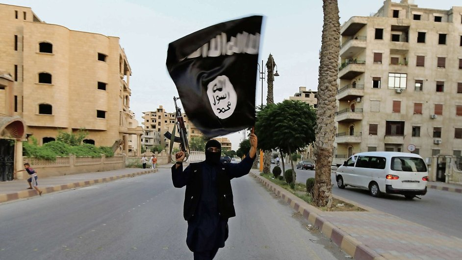 Příznivec Islámského státu s vlajkou ISIL v syrském městě Rakka, které teroristé kontrolují.