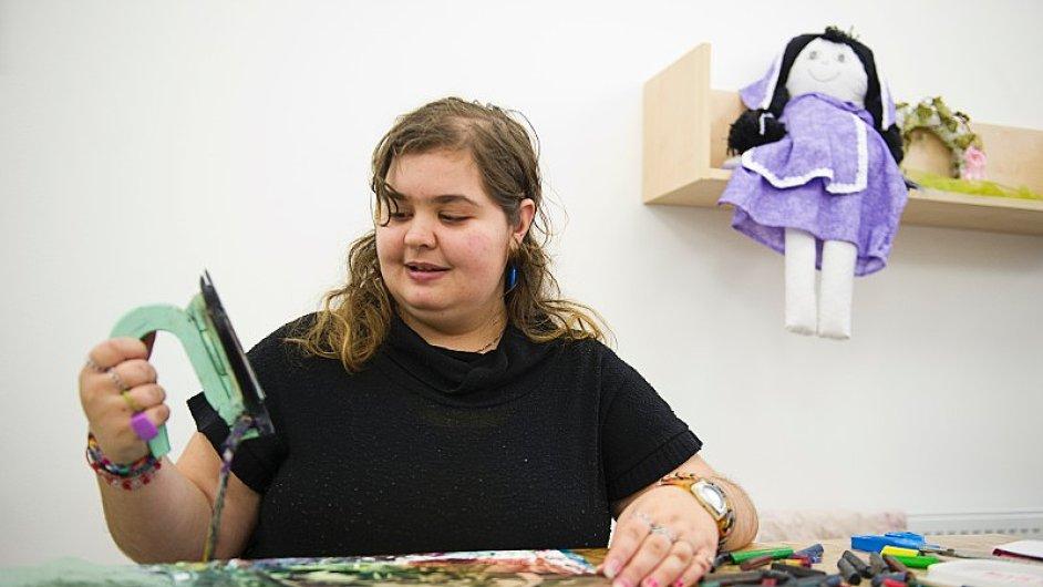 Jak vzniká obrázek: Klientka domova Sabina předvádí návštěvě, jak vznikají obrázky z voskovek.