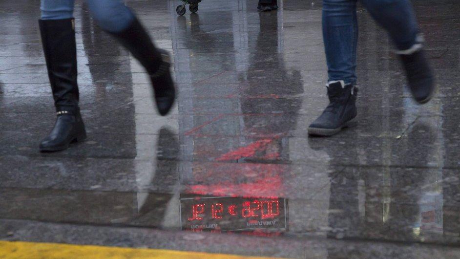 Kurz rublu se zrcadlí na mokrém chodníku.