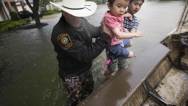Harvey - drama v Texasu. Nasnímku pomáhá dočlunu dvěma dětem šerif Troy Nehls zokresu Fort Bend ležícího 55 kilometrů jihozápadně odHoustonu.