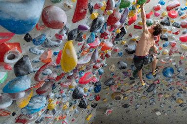 Adam Ondra na lezecké stěně.