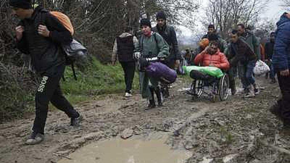 Uprchlíci na makedonsko-řeckém pomezí se snaží obejít hraniční plot.